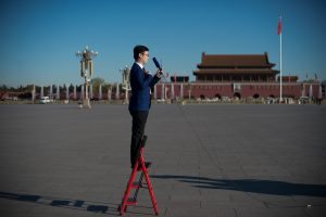 A television journalist stands on a ladder as he reports ahead of the CPPCC Closing ceremony at the Great Hall of the People in Beijing on March 13, 2017. More than 3000 delegates from across China are attending the annual meeting of the country's rubber-stamp congress. / AFP PHOTO / NICOLAS ASFOURI