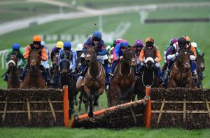 'Arctic Gold' ridden by jockey Tom Humphries crashes through a hurdle in The Pertemps Network Final Handicap Hurdle Race on the third day of the Cheltenham Festival horse racing meeting at Cheltenham Racecourse in Gloucestershire, south-west England, on March 16, 2017. / AFP PHOTO / GLYN KIRK