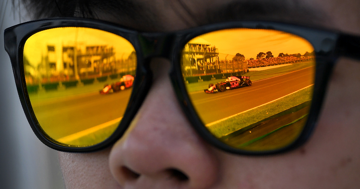 A Red Bull Racing car is reflected in a man's sunglasses during the first practice session at the Formula One Australian Grand Prix in Melbourne on March 24, 2017.  / AFP PHOTO / WILLIAM WEST / -- IMAGE RESTRICTED TO EDITORIAL USE - STRICTLY NO COMMERCIAL USE --