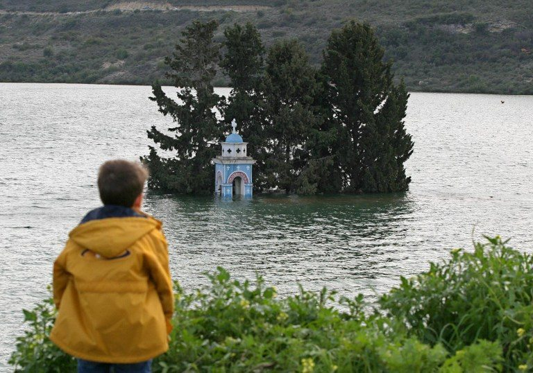 A boy looks at the belfry of the submerged church of Alassa village which lies in Cyprus' largest dam, Kouris, 23 February 2004. Kouris which holds almost half of the island's dammed water has never been so full, with just 5 million of its 115 million cubic metre capacity left to fill. Record rainfall over the past two years has helped replenish the water reserves on the island which had suffered severe drought in previous years.        AFP PHOTO/Philip MARK / AFP PHOTO / PHILIP MARK