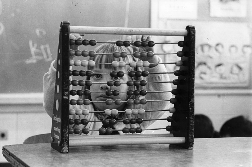 circa 1960:  A Haole girl learns to count on an abacus, the Chinese method of addition.  (Photo by John Titchen/Three Lions/Getty Images)
