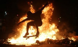 RIO DE JANEIRO, BRAZIL - MARCH 15: A young man practices a skateboarding move in front of a fire set by protestors following a demonstration against proposed federal government reforms on March 15, 2017 in Rio de Janeiro, Brazil. Protestors rallied nationwide, mostly peacefully, against proposed rules tightening pensions as the country continues to suffer through a financial and political crisis. (Photo by Mario Tama/Getty Images)