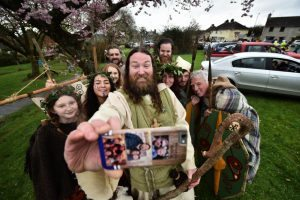 DOWNPATRICK, NORTHERN IRELAND - MARCH 17: Saint Patrick, played by actor Marty Burns takes a selfie along with members of the Magnus Vikings Association before they part in the cross community Saint Patrick's Day parade on March 17, 2017 in Downpatrick, Northern Ireland. Tradition holds that Saint Patrick and his companions landed at the mouth of the Slaney river, a few miles from Down Cathedral, in 432 AD. From here Patrick travelled extensively spreading the teachings of Christianity before his death on 17th March 461 AD. He is buried at nearby Down Cathedral. (Photo by Charles McQuillan/Getty Images)